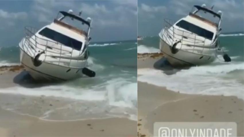 Un yate con personas a bordo encalla en la orilla de la playa en Miami Beach
