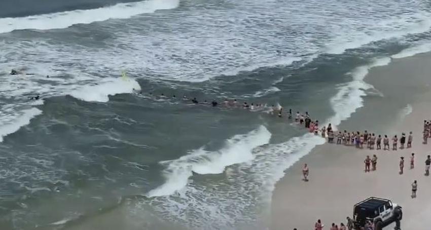 Bañistas forman una cadena humana para rescatar a una persona de las corrientes de resaca en Panama Beach, Florida