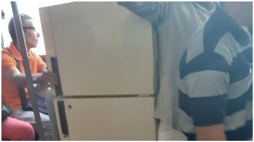 Cubano traslada un refrigerador en una guagua en La Habana