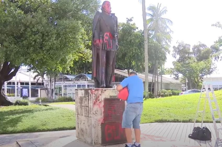 Cubano residente en Miami limpia los símbolos comunistas pintados en las estatuas vandalizadas en el Downtown