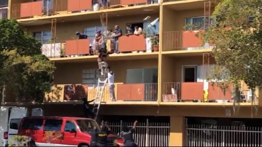 Por las ventanas y los balcones varias personas intentan escapar de un incendio en un edificio en North Miami