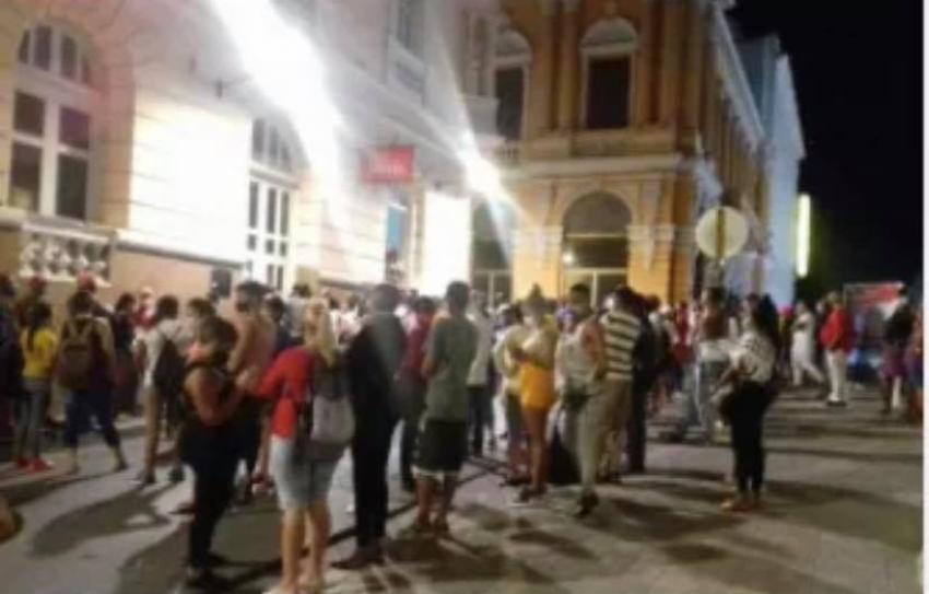 Santiagueros aglomerados en una cola de noche para poder comprar en una tienda en MLC